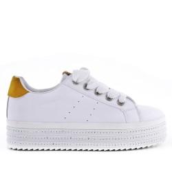 Tenis blanco con suela gruesa.